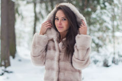Winter portrait of a beautiful woman in fur coat outdoors. Royalty Free Stock Photo