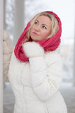 Winter portrait of beautiful woman. In pink scarf and white coat. Blonde lady with green eyes Royalty Free Stock Images