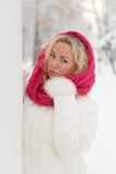 Winter portrait of beautiful woman. In pink scarf and white coat. Blonde lady with green eyes Royalty Free Stock Photos