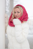 Winter portrait of beautiful woman. In pink scarf and white coat. Blonde lady with green eyes Stock Photography