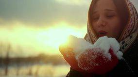 Winter portrait of a beautiful young woman blows snowflakes and smiling in slow motion during sunset time with lens stock video
