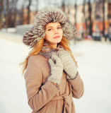 Winter portrait beautiful young woman wearing coat jacket and hat over snow Royalty Free Stock Images