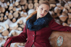 Winter portrait of blonde woman on firewood background Stock Photography
