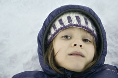 Winter Portrait. Close-up portrait of a child resting on the snow covered ground Royalty Free Stock Images
