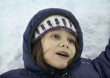 Winter Portrait. Close-up portrait of a child resting on the snow covered ground Royalty Free Stock Image