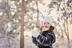 Winter portrait of cute child girl in fur coat on the walk in snowy forest Stock Photos