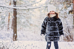 Winter portrait of cute happy child girl in grey fur coat. In snowy sunny forest royalty free stock photos