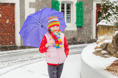 Winter portrait of a cute little girl under the snowfall Stock Image