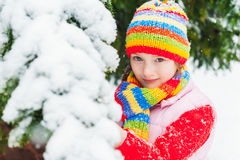 Winter portrait of a cute little girl under the snowfall Stock Photo