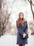 Winter portrait of a cute redhead lady in grey coat and scarf posing in the park. Winter portrait of a cute redhead lady in grey coat and scarf strolling in the royalty free stock photo