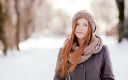 Winter portrait of a cute redhead lady in grey coat and scarf posing in the park Royalty Free Stock Image