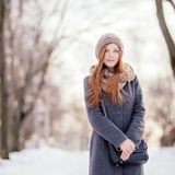 Winter portrait of a cute redhead lady in grey coat and scarf posing in the park. Winter portrait of a cute redhead lady in grey coat and scarf strolling in the royalty free stock photos