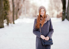 Winter portrait of a cute redhead lady in grey coat and scarf posing in the park Royalty Free Stock Images