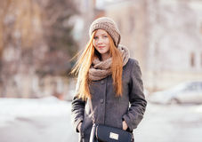 Winter portrait of a cute redhead lady in grey coat and scarf posing on the street Stock Photo