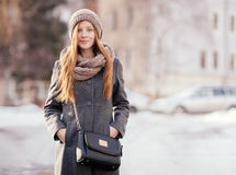 Winter  portrait of a cute redhead lady in grey coat and scarf posing on the street Royalty Free Stock Photography