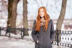 Winter portrait of a cute redhead lady in grey coat and scarf walking in the park Royalty Free Stock Image
