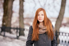 Winter portrait of a cute redhead lady in grey coat and scarf walking in the park Stock Photography