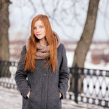 Winter portrait of a cute redhead lady in grey coat and scarf walking in the park Royalty Free Stock Photos