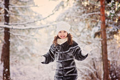 Winter portrait of cute smiling child girl on the walk in sunny snowy forest Royalty Free Stock Image