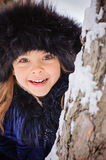 Winter portrait of cute smiling child girl on the walk in sunny snowy forest Stock Photography