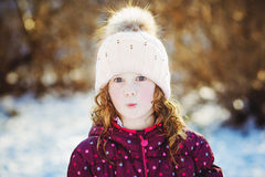 Winter portrait funny little girl in sun backlight. Stock Image