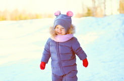 Winter portrait funny smiling child walking in snowy Royalty Free Stock Image