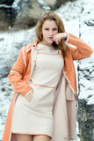Winter portrait of the girl. A bright orange coat Stock Images