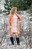 Winter portrait of the girl. A bright orange coat Stock Photos