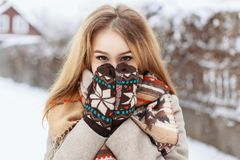 Winter portrait of a girl hiding in her scarf on the background. Of the village Royalty Free Stock Photography