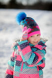 Winter portrait of girl. Winter portrait of girl of younger school age. Child is warmly dressed in a bright motley jacket and a cap. Mittens on hands. Girlie Stock Images