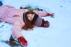 winter portrait of happy child girl playing outdoor in snowy garden, making snow angel. stock photos