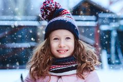 Winter portrait of happy child girl playing outdoor in snowy garden. Seasonal holidays and vacations concept royalty free stock images