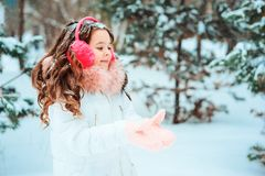 Winter portrait of happy kid girl in white coat and hat and pink mittens playing outdoor royalty free stock photos