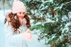 Winter portrait of happy kid girl in white coat and hat and pink mittens playing outdoor stock images