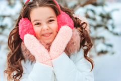 Winter portrait of happy kid girl in white coat and hat and pink mittens playing outdoor royalty free stock photo