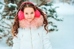 Winter portrait of happy kid girl in white coat and hat and pink mittens playing outdoor royalty free stock image