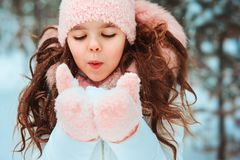 Winter portrait of happy kid girl in white coat and hat and pink mittens royalty free stock image