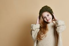 Winter portrait of happy little girl wearing knitted hat and sweater. stock photos