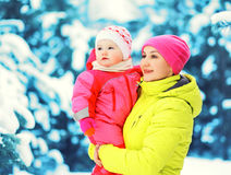 Winter portrait happy mother holds baby on hands over snowy christmas tree Royalty Free Stock Images