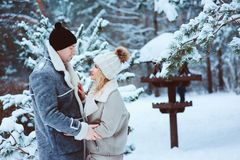 Winter portrait of happy romantic couple embracing and looking to each other outdoor in snowy day royalty free stock image