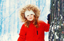 Winter portrait happy smiling little girl child near tree over snowy Royalty Free Stock Photography