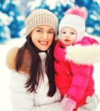 Winter portrait happy smiling mother and baby on hands over snowy christmas tree Royalty Free Stock Image
