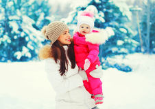 Winter portrait happy smiling mother with baby on her hands over snowy christmas tree. Background royalty free stock image