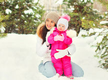 Winter portrait happy smiling mother with child over snowy christmas tree snowflakes. Background Stock Image