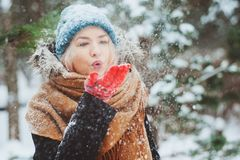 Winter portrait of happy young woman walking in snowy forest in warm outfit royalty free stock image