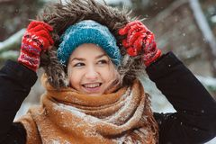 Winter portrait of happy young woman walking in snowy forest in warm outfit royalty free stock photography