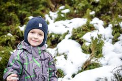 Winter portrait of kid boy in colorful clothes, outdoors during snowfall. Active outoors leisure with children in winter on cold s Royalty Free Stock Images