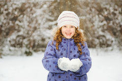Winter portrait of a little smiling girl, holds in its hands sno Stock Image