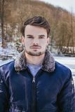 Winter portrait of man in casual clothes in snowy forest with frozen lake on background in winter time. Handsome guy with beard wi. Th aviator jacket posing to stock photo