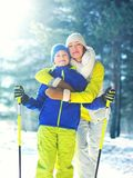 Winter portrait of mother hugs her son child on a ski. In the forest Stock Image
